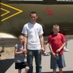 Corrie, Justin, and Nick standing up against some Russian plane